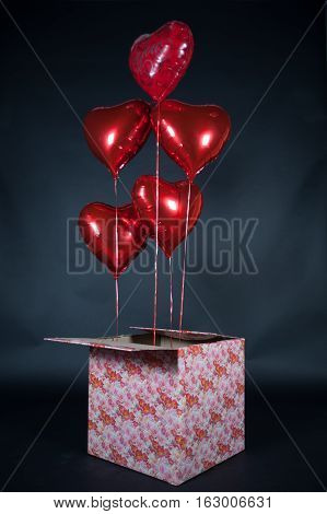 Festive balloons in the shape of hearts flew out of the box