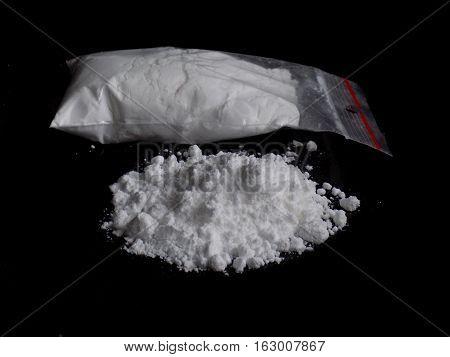 Cocaine drug powder pile and bag on black background
