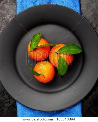 Ripe Orange Tangerines With Green Leaves On Black ,matt Plate , Top View. Concept Of Healthy Nutriti