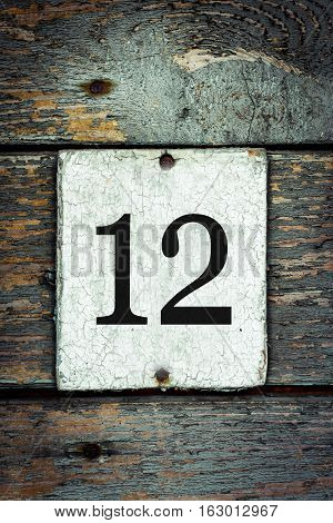 Old house number plate 12 on old grungy green painted door
