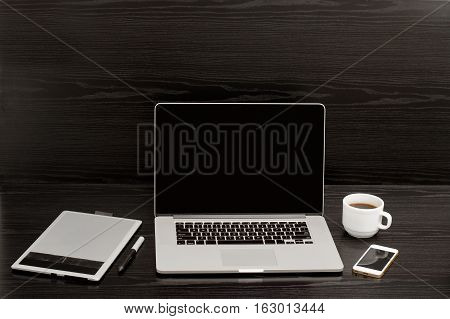 Open the laptop mug of coffee a telephone and a graphics tablet on a black background