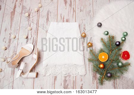 Lacy white skirt and white shoes on a wooden background Christmas balls on fir branch. Fashionable concept top view