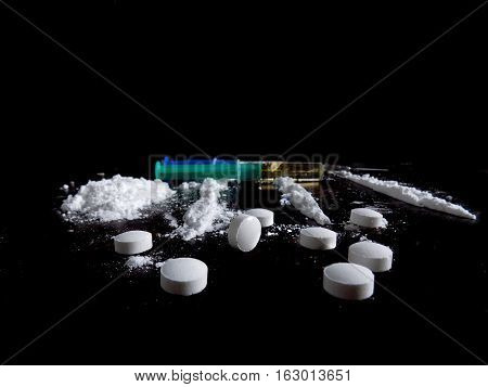 Cocaine drug powder pile and lines, injection and pills on black background