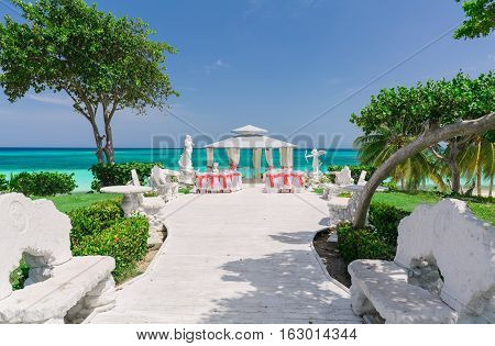 beautiful amazing gorgeous view of wedding ceremony event decorated gazebo against blue sky and ocean background in tropical garden near the beach