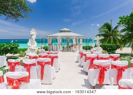 beautiful amazing view of wedding ceremony event decorated gazebo against blue sky and ocean background on tropical beach