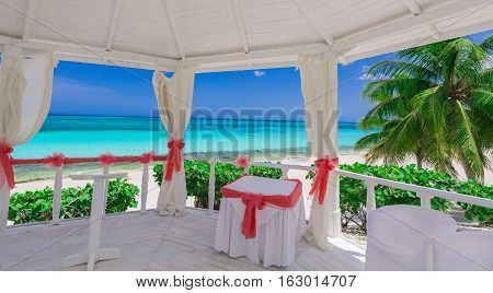 beautiful amazing, stunning inviting view from the inside of decorated wedding gazebo on tropical beach tranquil ocean and blue sky background