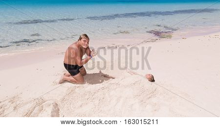 young adolescent, teenage boy playing with little girl on tropical beautiful beach near the ocean