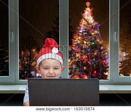 Small boy sitting near a laptop in the cap of Santa Claus