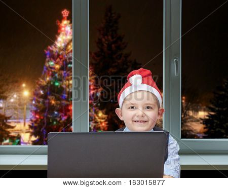 The child sits near the laptop on the background of the Christmas tree outside the window