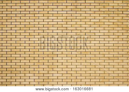 High resolution texture of a yellow brick wall background in the countryside rough blocks of stone brick masonry horizontal color technology architecture wallpaper.
