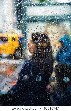 Rain in the city. Blurred scene of urban life. Emotional abstract background with defocused people and water drops on the streets of New York on a rainy day
