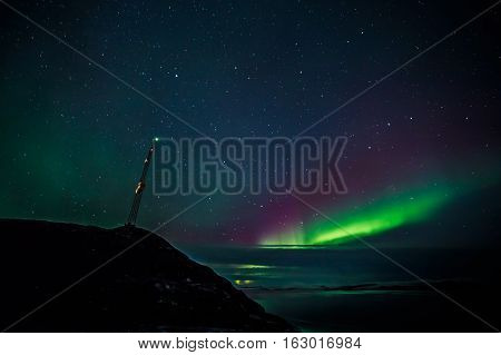 Radio Tower On The Hill And Northern Lights Covered By Clouds Over The Fjord In The Background