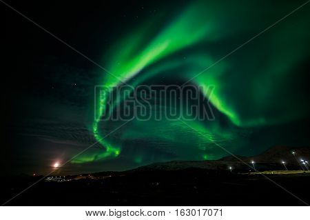 Northern lights and the rising Moon nearby nuuk city Greenland