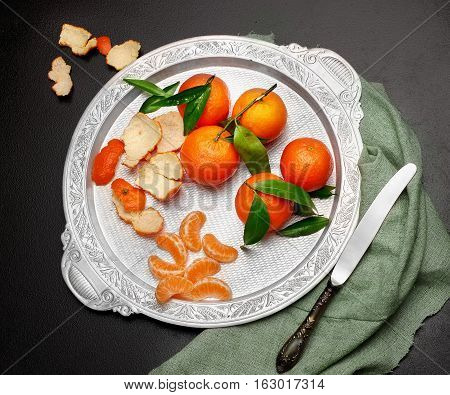 Still Life.fresh Tangerine Clementine With Leaves In Silver Tray On Dark Stone Background, With Knif
