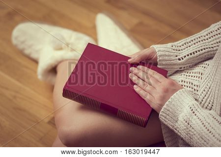 Detail of a young woman holding a closed book in her lap enjoying winter time in a cozy home atmosphere
