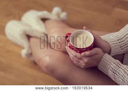 Close up of woman's hands holding a cup of coffee wearing a white sweater and home boots and enjoying the leisure time