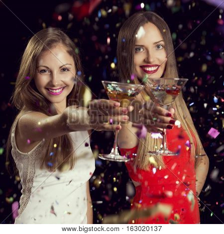 Two beautiful young women having fun at a party holding martini glasses and making a toast