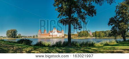 Mir, Belarus. Picturesque Panoramic View Of Mir Castle Complex From Side Of Lake In Summer. Architectural Ensemble, Ancient Gothic Monument, Unesco Heritage, Famous Landmark Under Blue Sky.