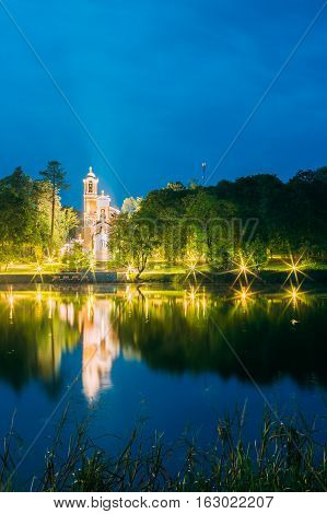 Mir, Belarus. View From Side Of Evening Lake Of Chapel And Burial Vault Of Svyatopolk-Mirsky Family In Bright Illumination. Part Of Architectural Ensemble Of Mir Castle Complex Under Blue Sky. poster