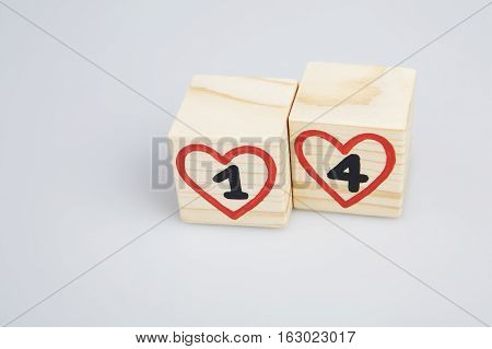 Wooden cubes with handwritten 14th and red hearts. Empty space.