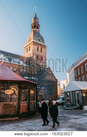Riga Latvia - December 1 2016: People Walking Near Christmas Market On Dome Square With Riga Dome Cathedral. Trading Houses With Sale Of Christmas Gifts Sweets And Mulled Wine. Famous Landmark.