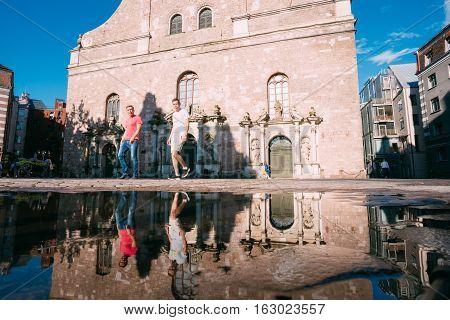 Riga Latvia - July 1 2016: Bottom View Of Two Young Men Walking On Cobbled Street Near St. Peter Church And Their Reflection In The Puddle After Rain Sunny Summer Day Blue Sky.