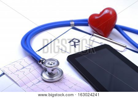 Closeup of stethoscope on a rx prescription and phone.