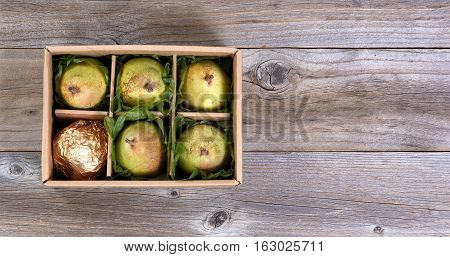 Overhead view of fresh pears in gift box on rustic wood with copy space.