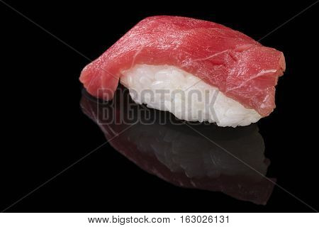 Close-up of Maguro sushi with tuna on a black background with reflection