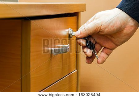 The man closes the drawer of the desk