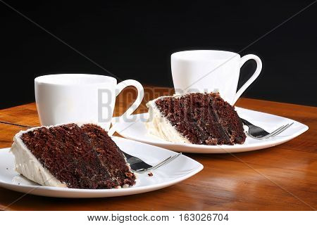 A slice of rich moist chocolate cake on a white plate with layers held in place with toothpicks