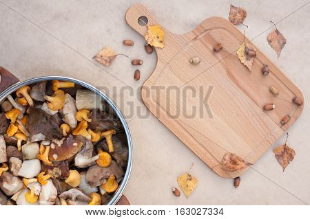 Clean Raw Fresh Edible Mushrooms Chanterelle And Cut Large Pieces Of Porcini In Large Metal Kitchen Pot Pan And Cutting Wooden Board With Autumnal Oaks And Leaves On Beige Brown Background. Top View.