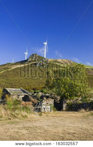 Spain Asturias ancient farm in the foreground wind turbines in the background ancient and modern juxtaposition