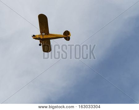 Mustard yellow colored small plane flying in the sky