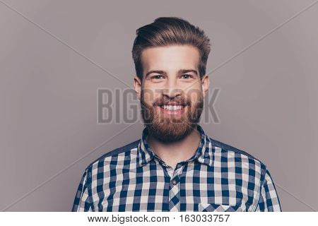 Portrait Of Handsome Smiling Young Man Looking At Camera Isolatet On Gray Wall