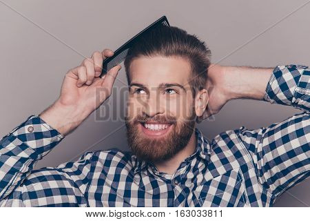 Portrait Of Stylish Cheerful  Glad Happy Handsome Cheerful Young Man Combing His Hair And Laugh
