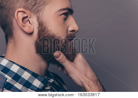 Side View Portrait Of Thinking Stylish Young Man Touch His Beard