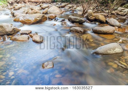 Smooth flowing water through the natural rock creek.