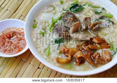 boiled rice porridge with pork entrails on bowl and chili paste