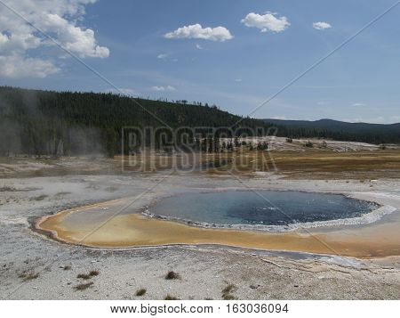 The hot water in Crested Pool in Yellowstone National Park boils from the intense geothermal heat on a summer day.