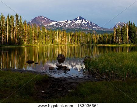 The forest and Three Sisters in Oregon's Cascade Mountains reflect in Scott Lake on a summer day at sunset.
