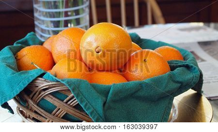 Basket of Cara Cara oranges sits on table in sunlight.