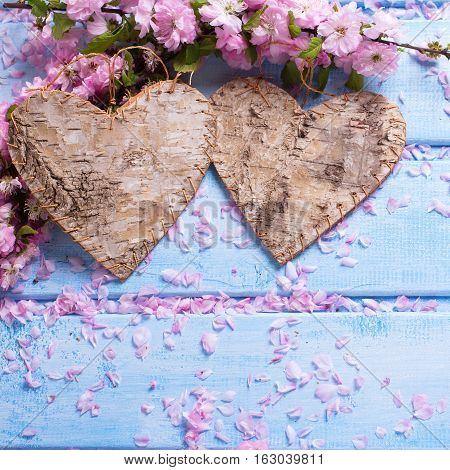 Two decorative hearts and pink sakura flowers on blue wooden background. Selective focus. Place for text. Square image.