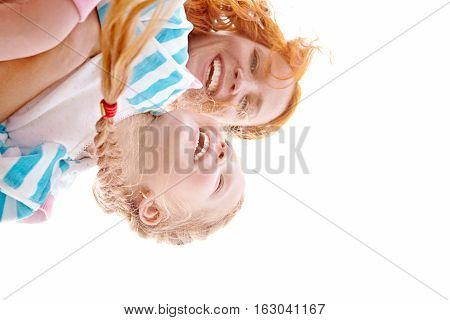 Young ginger mom and daughter laughing, playing outside
