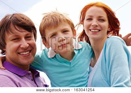 Portrait of young cheerful family smiling looking at camera