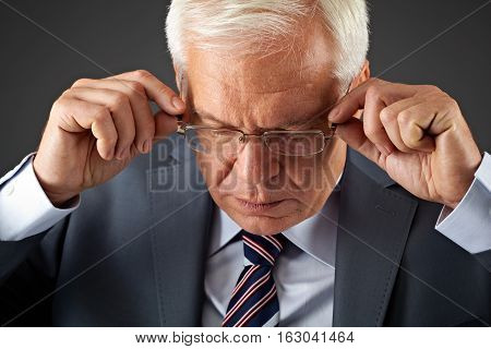 portrait of businessman adjusting eyewear on gray
