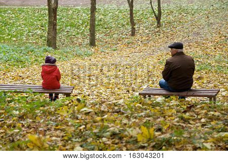 autumn. little girl and an old man sitting on a bench in the park