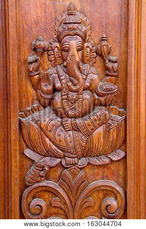 Teakwood door panel with bas relief etching of Ganesha