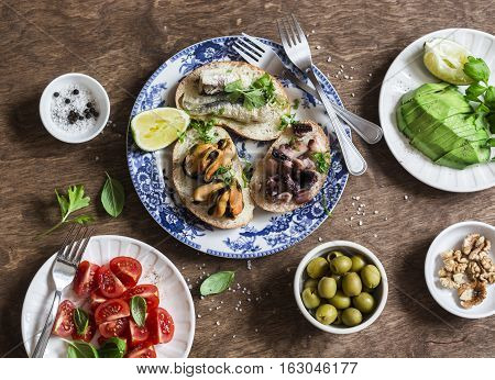 Delicious tapas - sandwiches sardines mussels octopus grape olives tomato and avocado on wooden table top view. Flat lay