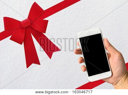 Red bow isolated on white clean fresh snow texture background with hand holding smartphone for your messages